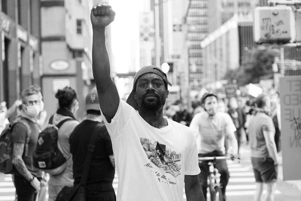 A man looking directly at the camera holds his fist in the air during a protest in New York City over the murder of George Floyd.