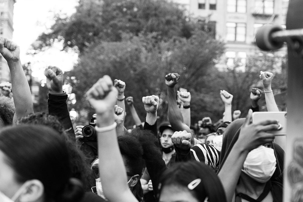 Multiple fists raised in the air during a protest in New York City over the murder of George Floyd.
