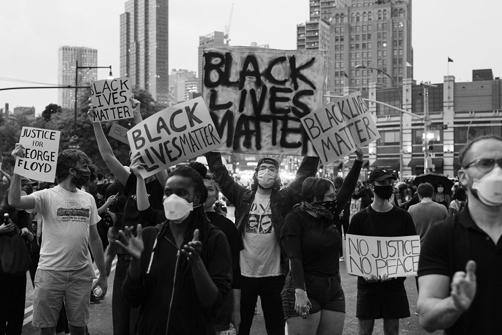 Protesters wearing masks for protection against the coronavirus carry signs saying 'Black Lives Matter,' 'Justice for George Floyd,' and 'No justice, no peace.'