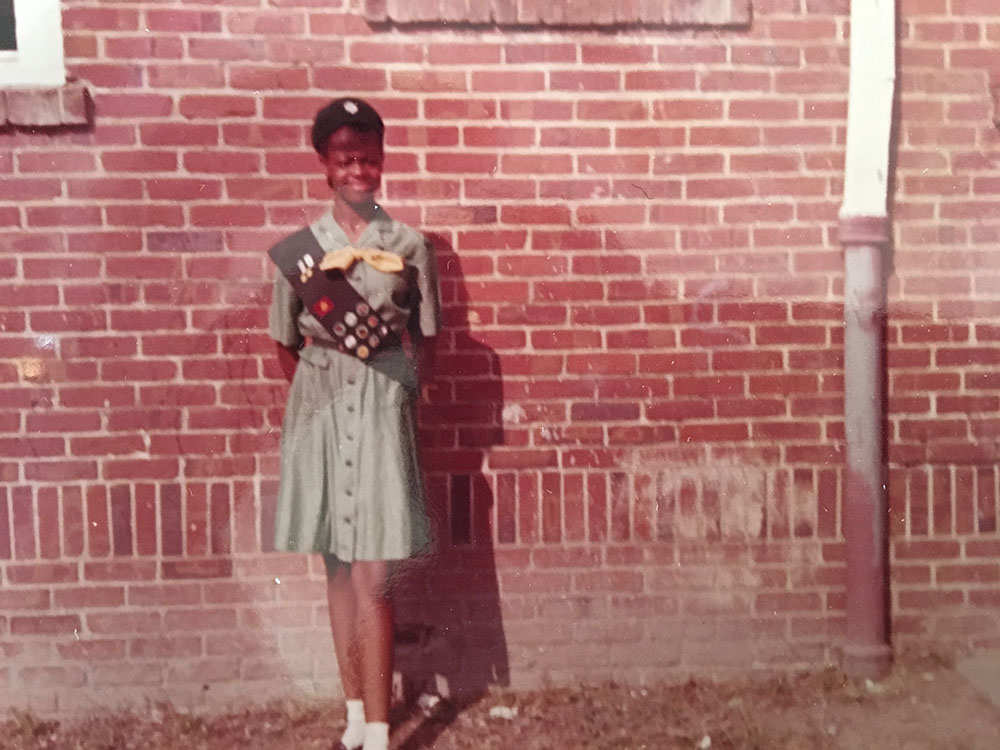 A girl wearing a girl scout uniform stands in front of a brick wall.
