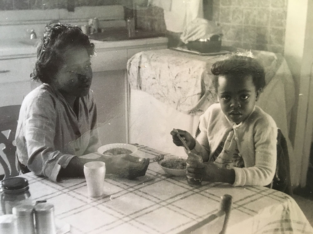 An older woman feeds her toddler daughter at a kitchen table.