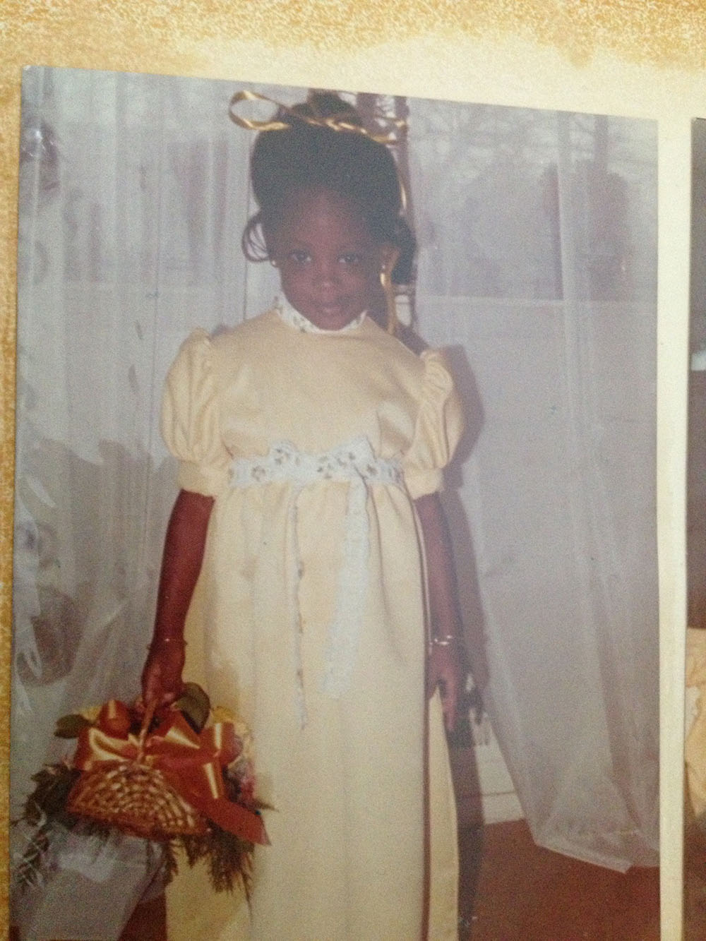 A young girl wearing a long formal dress holding a flower basket.